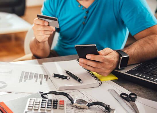 hombre con tarjeta de crédito y calculadora